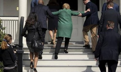 Hillary getting helped up stairs